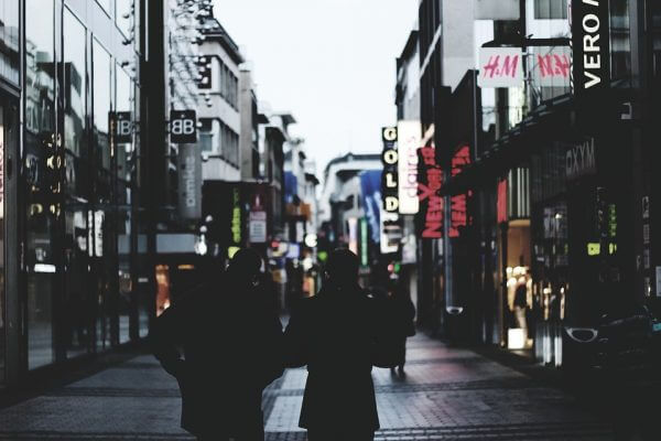 Two people walking down a high street