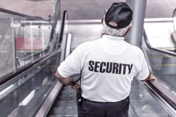 A security guard going down an escalator