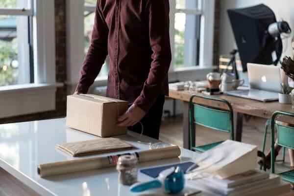 A person going to open a package in the office