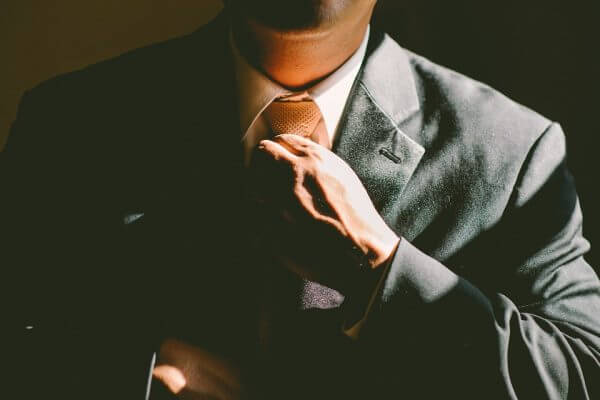 Close up of a man tightening his suit tie