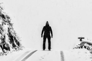 A man dressed in black standing in the snow