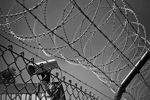 A cctv camera behind a barbed wire fence