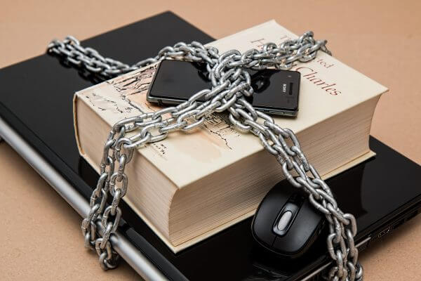 a laptop, book and phone locked in chains