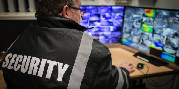 Security man looking at surveillance camera footage