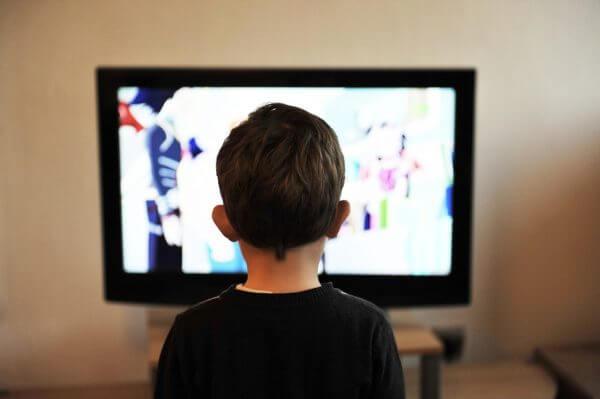 A little boy watching the TV