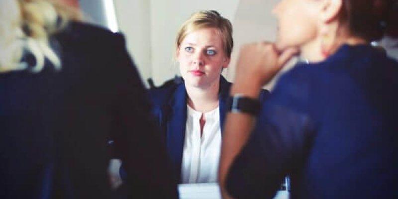 Employee sitting opposite two women